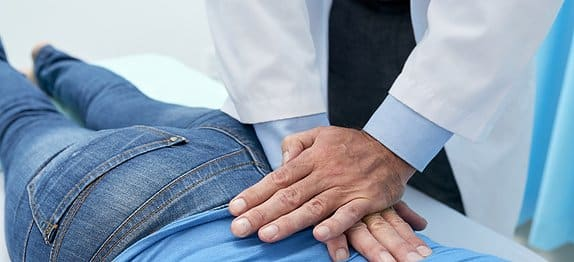 Doctor helping patients with lower back pain.