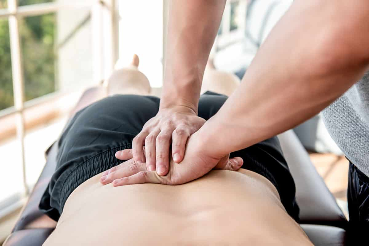 Therapist doing a low back massage to sportsman