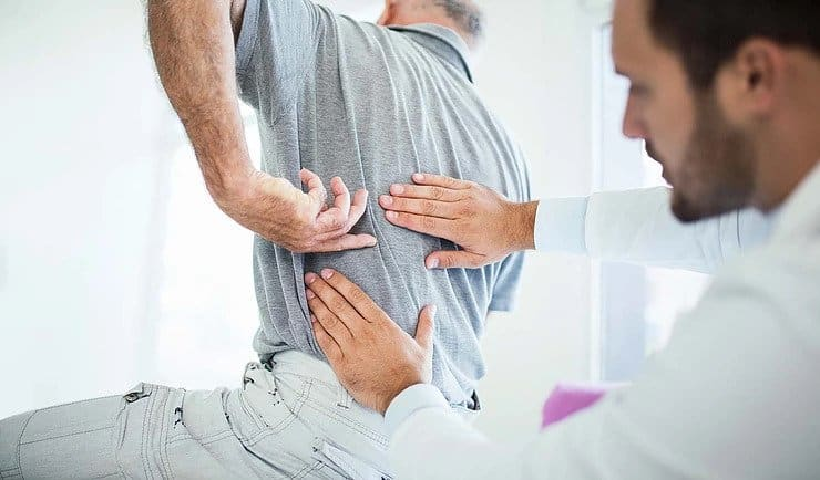 Doctor examining middle back pain to elderly man