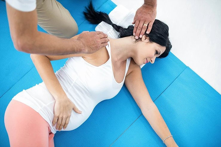 Chiropractic doctor helping a pregnant woman with her neck pain