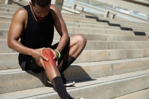 Cropped portrait of dark-skinned jogger in training socks and running shoes having sprain, clutching his injured knee, massaging it with both hands after intense workout in urban surroundings