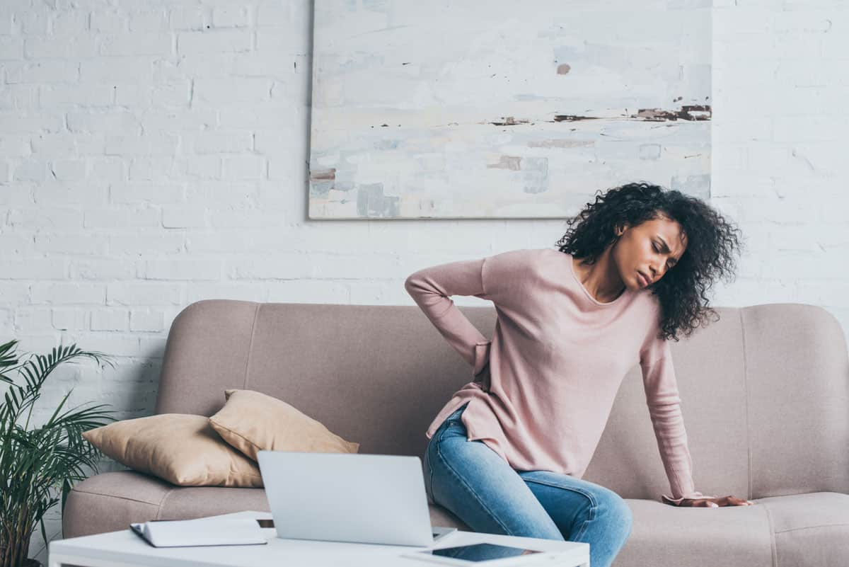 unhappy african american woman suffering from back pain while sitting on sofa near table with digital devices