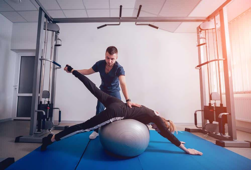 Beautiful young woman doing exercises with ball under supervision of physiotherapist